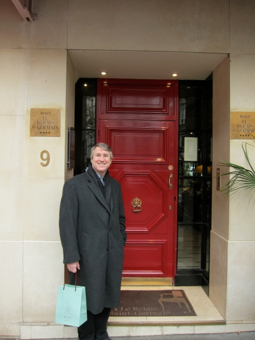 Mark standing by happy red door of nice hotel