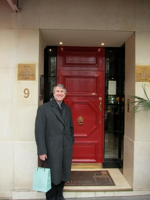 Mark standing by happy red door of nice hotel